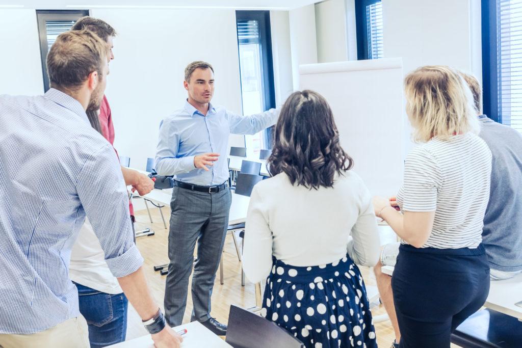 Lehrender diskutiert mit kleiner Gruppe Studierender